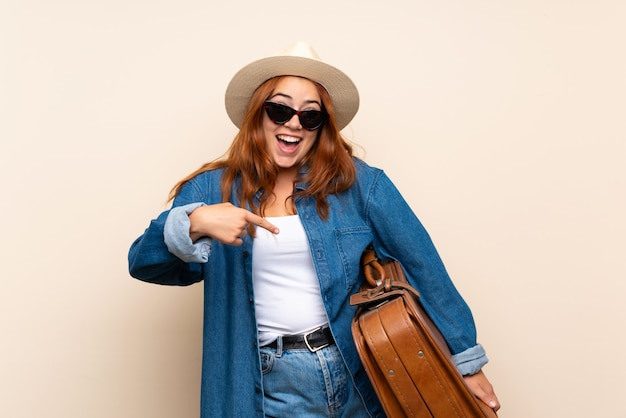 Redhead traveler girl with suitcase over isolated  with surprise facial expression
