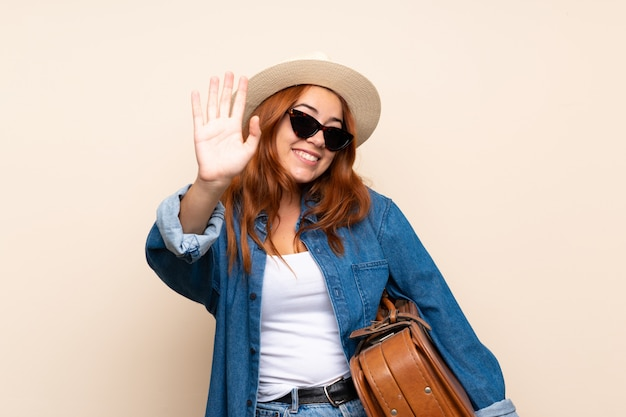 Redhead traveler girl with suitcase saluting with hand with happy expression