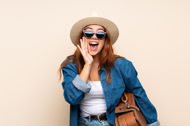 Redhead traveler girl with suitcase  shouting with mouth wide open