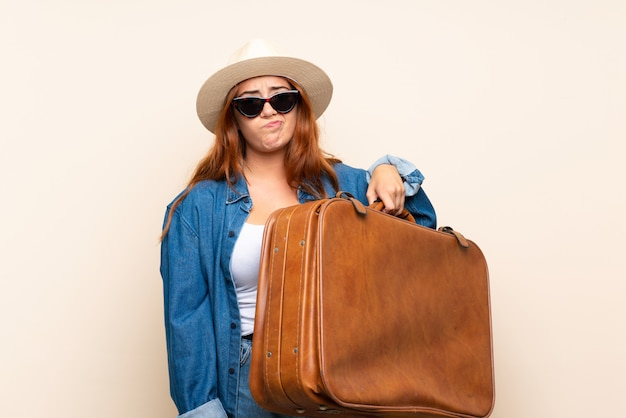 Redhead traveler girl with suitcase with sad expression
