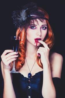 혈액의 유리를 가진 빨간 머리 뱀파이어 여자입니다. 빈티지 스타일의 사진.