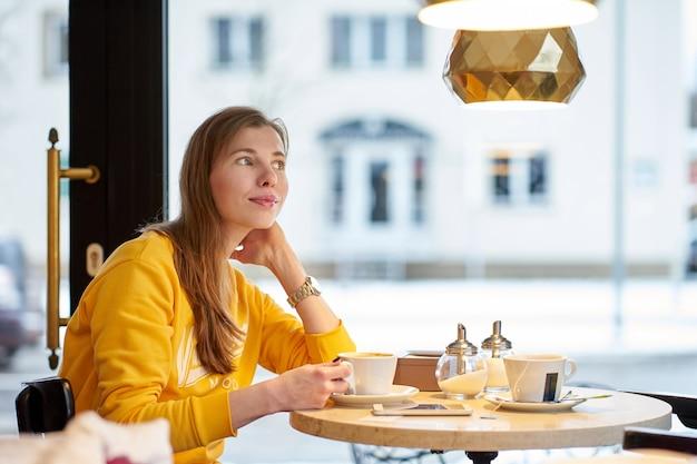 Рыжая белая девушка в желтом свитере пьет кофе в кафе и мечтает