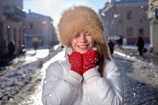 Рыжая белая тощая девушка, одетая в лисьей меховой шапке, милый зимний портрет.