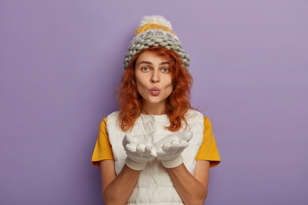 빨간 머리 여자는 카메라에 불면, 손바닥을 앞으로 유지하고, 니트 모자와 흰색 조끼를 입고, 겨울철을 즐깁니다.
