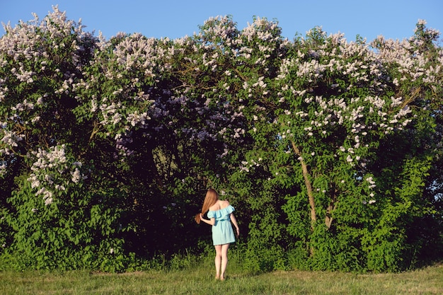Redhead woman in blue light cocktail dress standing in front of lilac bushes