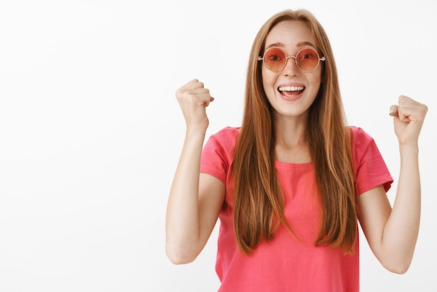 赤毛の女性が応援、握りこぶしで拳を高く上げて笑顔で嬉しそうに笑い続ける