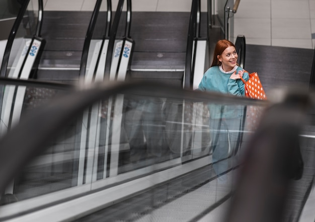 Redhead woman climbing escalator