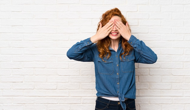 Redhead woman covering eyes by hands