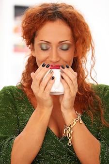 Redhead woman drinking coffee