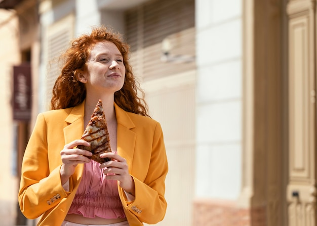 Redhead woman eating some street food