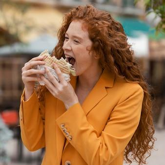 いくつかの屋台の食べ物を食べる赤毛の女性