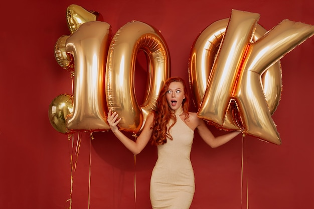 Redhead woman in elegant dress posing excited holding golden balloons on red