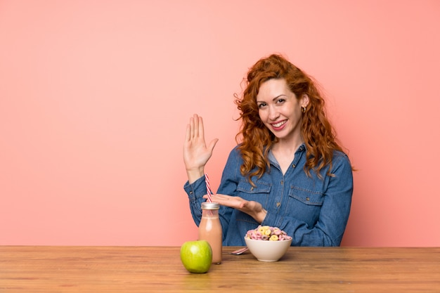 Redhead woman having breakfast cereals and fruit extending hands to the side for inviting to come