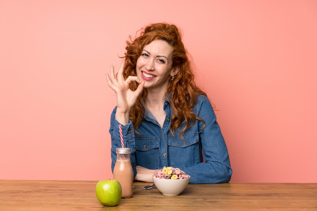 Redhead woman having breakfast cereals and fruit showing an ok sign with fingers