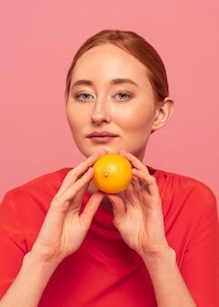 オレンジを保持している赤毛の女性