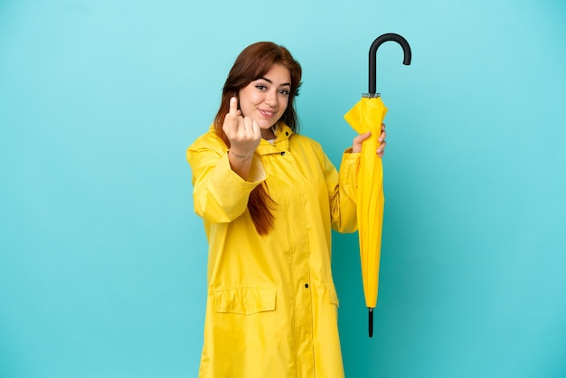 来るジェスチャーをしている青い背景で隔離の傘を保持している赤毛の女性