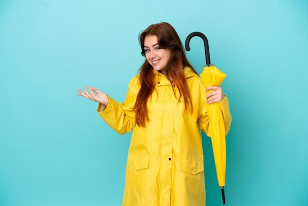来るように誘うために手を横に伸ばして青い背景で隔離の傘を持っている赤毛の女性