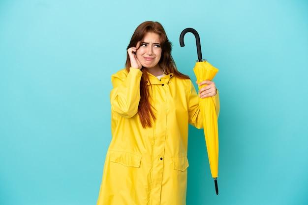 Рыжая женщина, держащая зонтик, изолированная на синем фоне, разочарована и закрывает уши