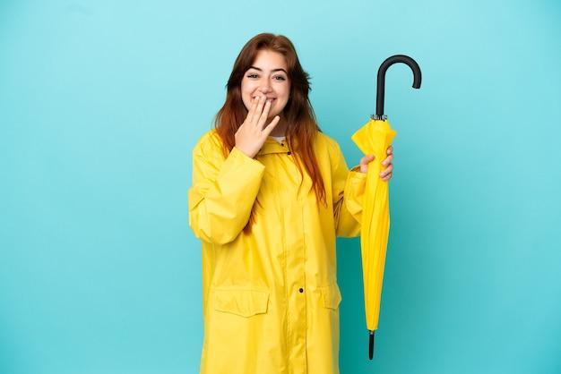 青の背景に分離された傘を持っている赤毛の女性幸せと笑顔の手で口を覆う