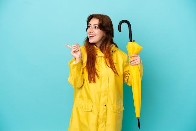 Рыжая женщина, держащая зонтик на синем фоне, намереваясь реализовать решение, подняв палец вверх