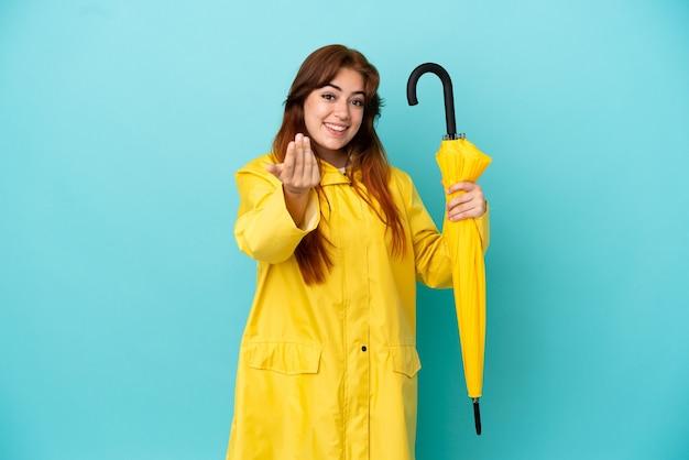 手で来るように誘う青い背景で隔離の傘を持っている赤毛の女性。あなたが来て幸せ