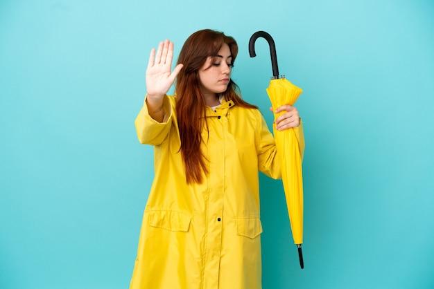 Рыжая женщина, держащая зонтик, изолированная на синем фоне, делает стоп-жест и разочарована