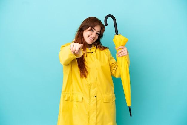 幸せな表情で正面を向いている青い背景に分離傘を保持している赤毛の女性