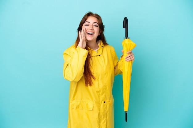 口を大きく開いて叫んで青い背景で隔離の傘を保持している赤毛の女性