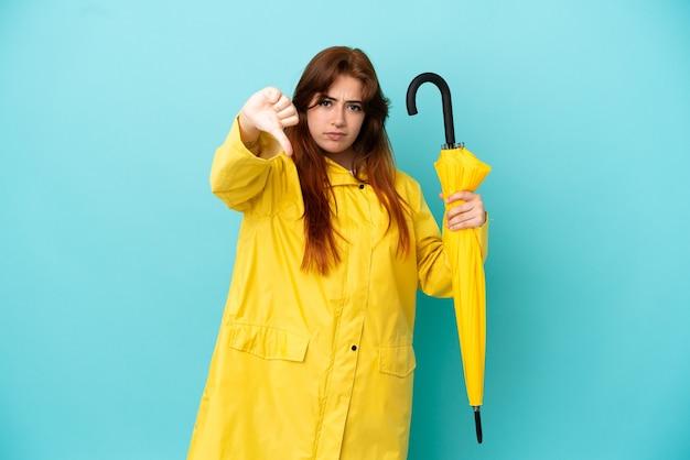 否定的な表現で親指を示す青い背景で隔離の傘を保持している赤毛の女性