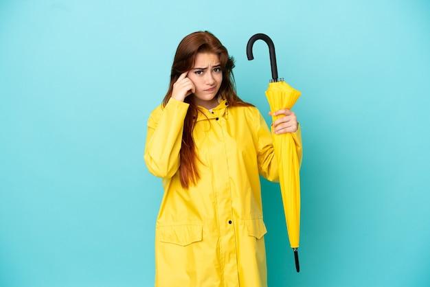 Рыжая женщина, держащая зонтик, изолированная на синем фоне, думает об идее