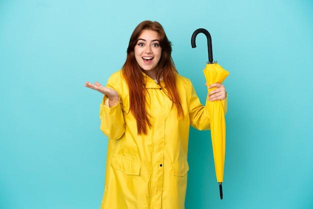 ショックを受けた表情で青い背景に分離傘を保持している赤毛の女性