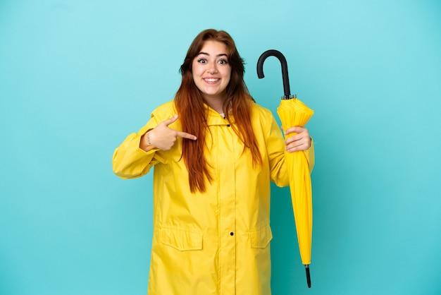 Рыжая женщина держит зонтик на синем фоне с удивленным выражением лица