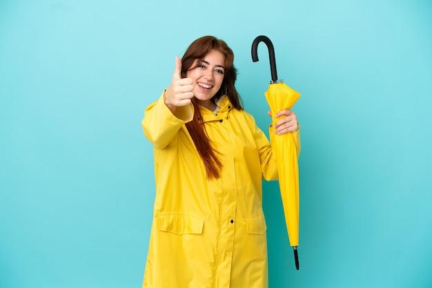 何か良いことが起こったので、親指を上にして青い背景で隔離の傘を持っている赤毛の女性