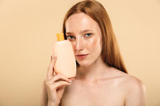 スキンケアのためのクリームを保持している赤毛の女性。