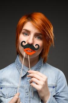 偽の口ひげと唇を保持している赤毛の女性