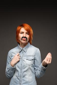 Рыжая женщина с поддельными усами морщась