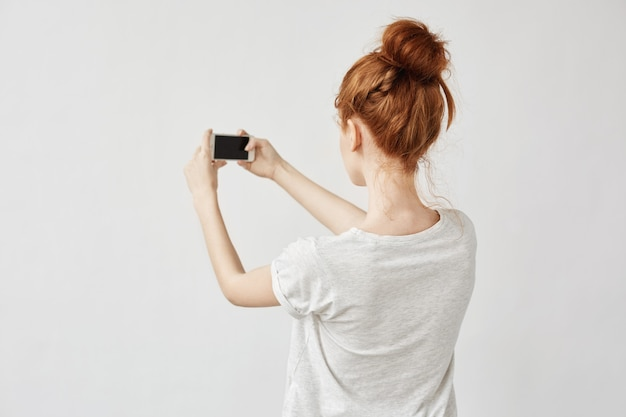 Redhead woman holding phone standing back.