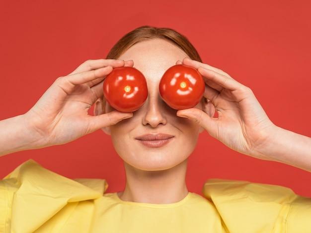 Pomodori della holding della donna della testarossa