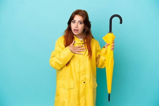 Redhead woman holding an umbrella isolated on blue background surprised and shocked while looking right