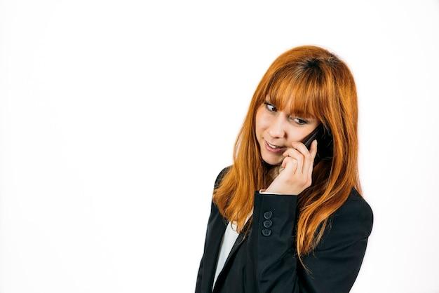 白い壁に隔離された携帯電話で話している黒いスーツの赤毛の女性