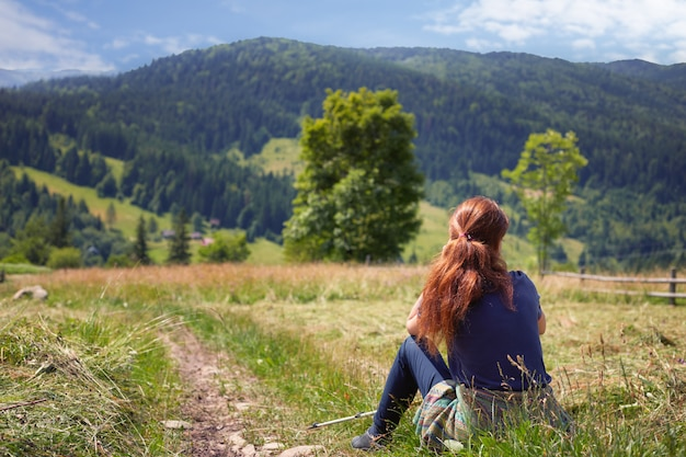 Рыжая женщина в синей футболке сидит на лугу в горной местности, лицом к горам и еловому лесу. девушка отдыхает после походов.