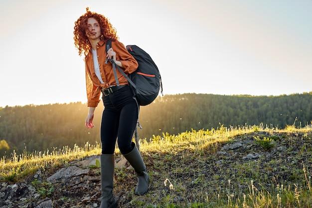 ハイキング旅行でカジュアルな服を着た赤毛の女性マウントの上を歩くバックパックを持つ美しい女性ハイカー...