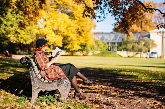 Рыжая женщина в клетчатом пальто и черном берете читает книгу на скамейке, отдыхая в осеннем парке на солнце ...