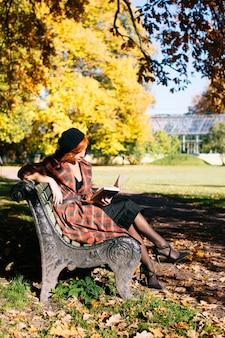 Рыжая женщина в клетчатом пальто и черном берете читает книгу на скамейке, отдыхая в осеннем парке в солнечный день