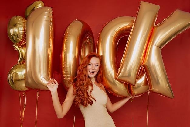 레드에 황금 풍선을 들고 흥분 포즈 우아한 드레스에 빨간 머리 여자