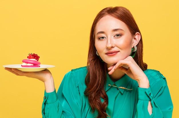 おいしいケーキを見せている緑のブラウスの赤毛の女性