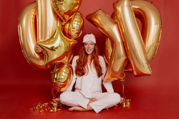 Рыжая женщина в пижаме, спальной маске и маске для сна позирует взволнованно, держа золотые шары на красном