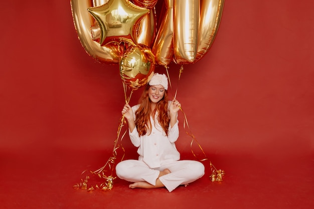 ピジャマとスリーピングマスクの赤毛の女性が赤に金色の風船を持って興奮してポーズをとる