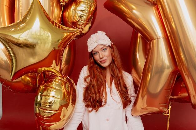 Рыжая женщина в пижаме и спящей маске позирует взволнованно, держа золотые шары на красном