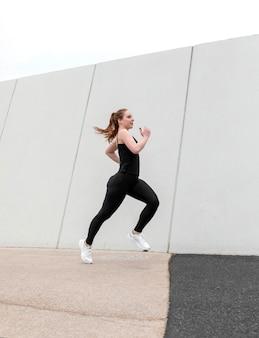 Рыжая женщина в спортивной одежде, упражнения на открытом воздухе